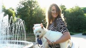 La mujer juguetona da vuelta alrededor a sostener dos perros de animales domésticos en manos C?mara lenta almacen de metraje de vídeo