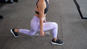 La mujer juguetona está haciendo las estocadas para las piernas con pesas de gimnasia en sus manos en el gimnasio, primer de las  almacen de metraje de vídeo