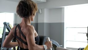 La mujer juguetona está haciendo los ejercicios para los músculos de la espina dorsal en el simulador del bloque metrajes