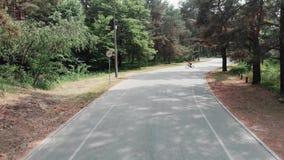 La mujer juguetona joven del triathlete comienza a montar su bici en un carril de bicicleta Opini?n del abej?n de Frontside almacen de metraje de vídeo