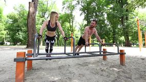 La mujer juguetona joven y el hombre barbudo que hacen pectorales ejercita en un parque