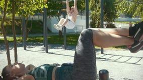 La mujer juguetona que hace aptitud ejercita delante del atleta muscular del hombre levantado en la barra al aire libre en el día metrajes