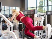 La mujer juguetona que usa pesos presiona la máquina para las piernas en el gimnasio fotos de archivo