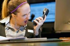 La mujer jura con el cliente por el teléfono fotos de archivo