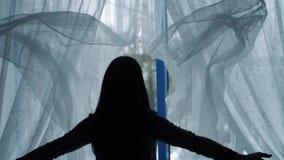 La mujer lanza hacia fuera las cortinas y la ventana abierta almacen de metraje de vídeo