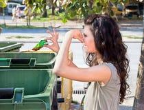 La mujer lanza la basura en contenedor Imagen de archivo libre de regalías