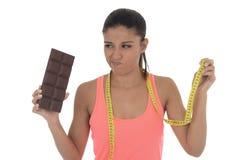 La mujer latina atractiva joven que sostiene la cinta de la medida de taylor y la barra de chocolate en la nutrición sana adietan foto de archivo