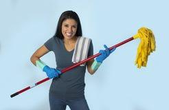 La mujer latina feliz atractiva joven en los guantes que se lavaban que sostenían la fregona que se divertía que cantaba y que ju imagen de archivo