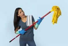 La mujer latina feliz atractiva joven en los guantes que se lavaban que sostenían la fregona que se divertía que cantaba y que ju fotos de archivo libres de regalías