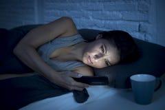 La mujer latina hermosa joven en cama en la noche que mandaba un SMS usando el teléfono móvil cansó tarde sueño descendente fotos de archivo