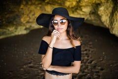 La mujer latina hermosa que piensa con el sombrero y las gafas de sol que toman el sol en rocas varan el tiempo de la vocación de Fotografía de archivo libre de regalías