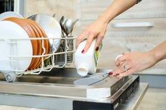 La mujer lava los platos en la máquina de lavaplatos fotos de archivo