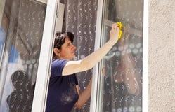 La mujer lava un cristal de ventana imagenes de archivo