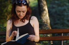 La mujer lee adentro el parque Imagen de archivo libre de regalías