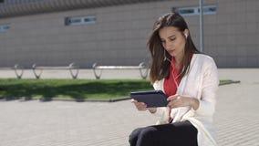 La mujer lee algo en su tableta que se coloca con la maleta roja almacen de metraje de vídeo