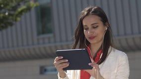 La mujer lee algo en su tableta que se coloca con la maleta roja almacen de video
