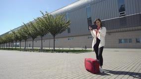 La mujer lee algo en su tableta que se coloca con la maleta roja metrajes