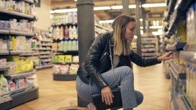La mujer lee la etiqueta en el paquete y la botella en el supermercado Buscando los productos de los estantes bajos y puestos le metrajes