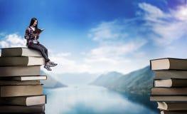 La mujer lee mientras que se sienta en una montaña de libros Foto de archivo