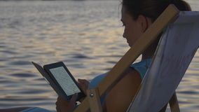 La mujer lee un eBook en la puesta del sol cerca del agua glaring