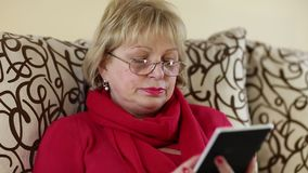 La mujer lee un libro La mujer mayor se sienta en un sofá y lee el libro electrónico almacen de video