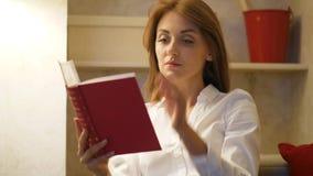 La mujer leyó el libro en casa, concepto libre de los artilugios almacen de video