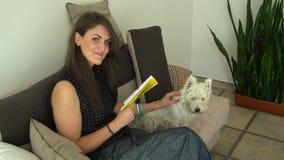 La mujer leyó la revista y el perro de la caricia mientras que esperaba en salón del peluquero del animal doméstico metrajes