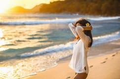 La mujer libre goza de la brisa del océano en la puesta del sol fotos de archivo