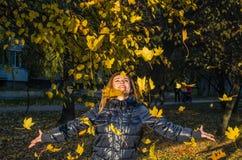 La mujer linda alegre joven de la muchacha que juega con amarillo caido del otoño se va en el parque cerca del árbol, riendo y so Fotos de archivo