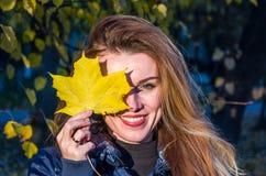 La mujer linda alegre joven de la muchacha que juega con amarillo caido del otoño se va en el parque cerca del árbol, riendo y so Imagenes de archivo