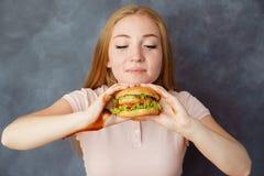 La mujer linda con la hamburguesa en manos disfruta del aroma fotos de archivo libres de regalías