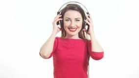 La mujer linda en escuchar rojo la música saca los auriculares grandes y el guiño a la sonrisa de la cámara aislada en el fondo b metrajes