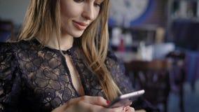 La mujer linda joven que usa el teléfono, sentándose en un café que sostiene un smartphone, contestando manda un SMS Mujer de neg metrajes
