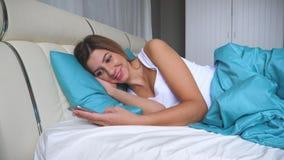 La mujer linda por la mañana que miente en una cama utiliza Smartphone Apps escribe mensajes almacen de video