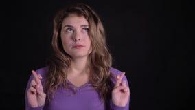 La mujer linda que gesticula los cruzar-fingeres firma en cámara para mostrar expectativas y esperanza en fondo negro almacen de metraje de vídeo