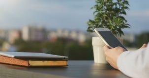 La mujer linda que usa el teléfono, sentándose en un café que sostiene un smartphone, los textos de contestación, llamadas de tel metrajes
