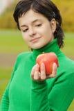 La mujer linda sonriente muerde la manzana madura Imagenes de archivo