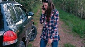La mujer llama en el teléfono y pide ayuda con un coche quebrado En una rabia golpea la rueda con el pie de un coche almacen de video