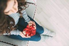 La mujer lleva a cabo el corazón de la caja de regalo Imagen de archivo