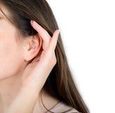 La mujer lleva a cabo su mano cerca del oído y escucha Imagen de archivo libre de regalías
