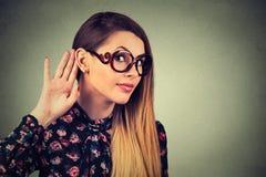 La mujer lleva a cabo su mano cerca del oído y escucha cuidadosamente Foto de archivo libre de regalías