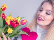 La mujer lleva a cabo tulipanes y el corazón rojo Foto de archivo