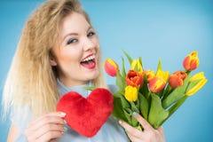 La mujer lleva a cabo tulipanes y el corazón rojo imágenes de archivo libres de regalías