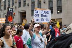 La mujer lleva el cartel durante el clima marzo, NYC de las 2014 personas Fotos de archivo libres de regalías