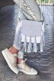 La mujer lleva una camiseta gris, zapatillas de deporte blancas y sostener el bolso blanco con la franja Imagenes de archivo