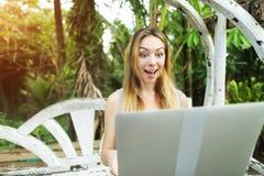 La mujer loca de la cara utiliza el ordenador portátil para los juegos onlines el día soleado, fondo de las palmas del verde de l Imágenes de archivo libres de regalías