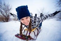 La mujer loca disfruta de un paseo del trineo El sledding de la mujer fotografía de archivo libre de regalías