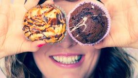 La mujer loca sonriente sostiene las tortas disponibles Fotografía de archivo