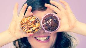 La mujer loca sonriente sostiene las tortas disponibles Fotos de archivo