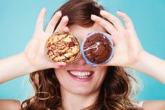 La mujer loca sonriente sostiene las tortas disponibles Foto de archivo